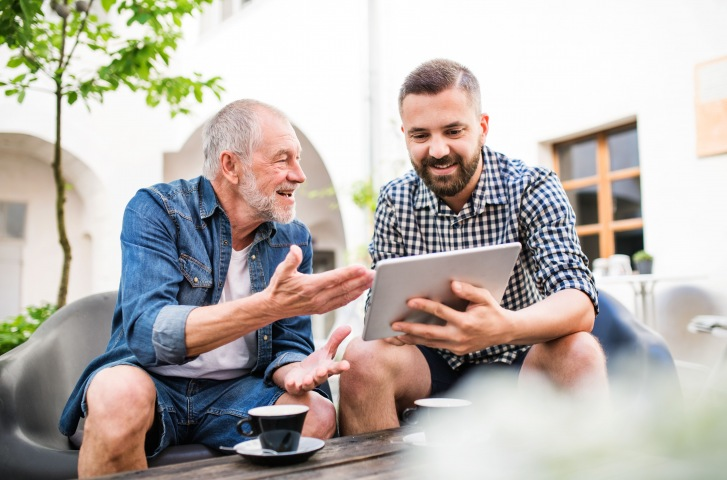 young man teaching a old man using tablet