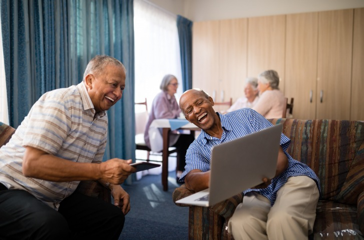 two-males-laughing-in-common-room-on-laptop-three-females-in-background-sitting-Overture
